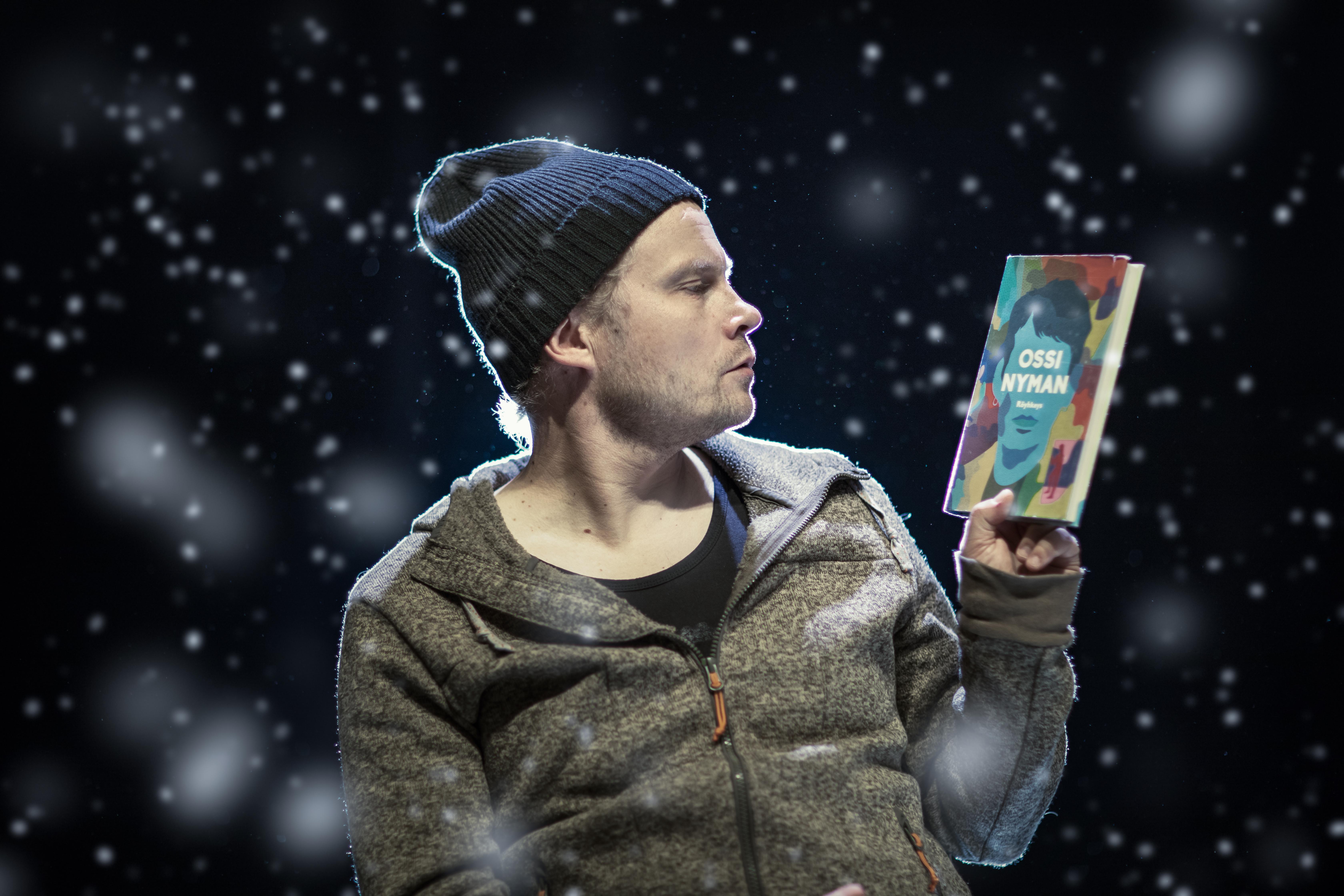 Näyttelijä Mikko Lauronen lukemassa kirjaa.