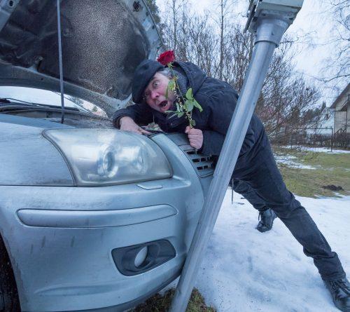 Taiteilija Henry Räsänen ilmeilee auton äärellä punainen ruusu kädessään
